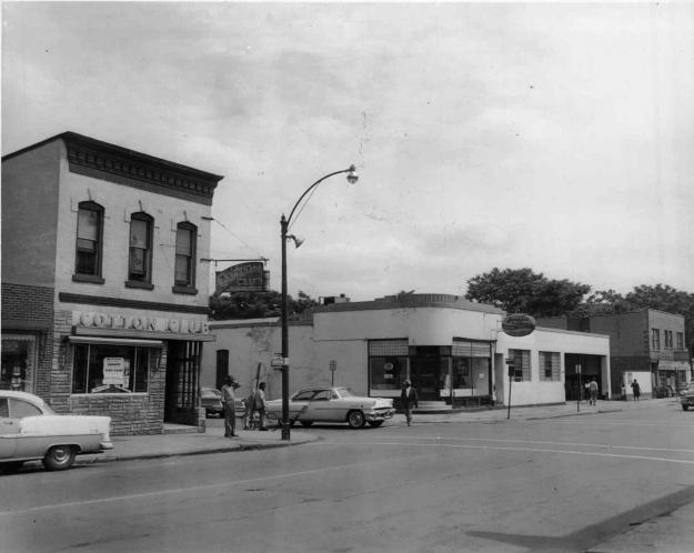 A black and white photo shows the Cotton Club on the street it once stood on. Cars are driving by.