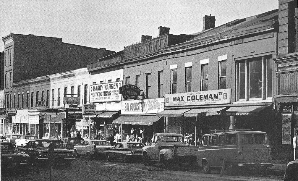 A black and white photo shows Rochester's Front Street in the 60s; it appears busy, with lots of well-advertised storefronts and cars driving by.