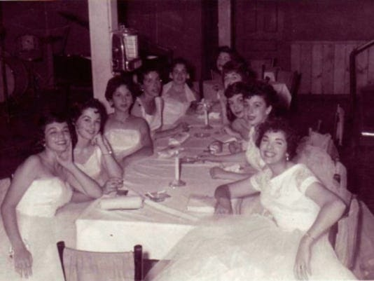 A group of young women in white dresses sit at a long banquet table.