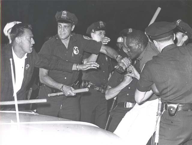 Police officers armed with batons restrain a Black man during the July 1964 Rochester riots.