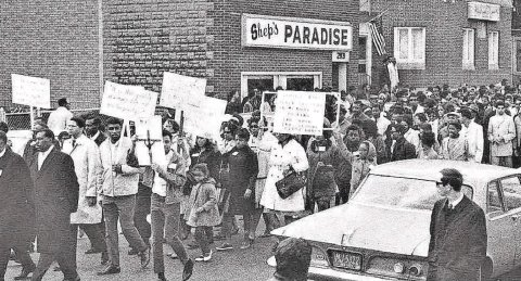3,000 people marched on Clarissa Street following the funeral of Martin Luther King Jr. Shep's Paradise, another club, is pictured in the background. The demonstrators are holding signs, most are African Americans. A 1950's car is in the foreground.