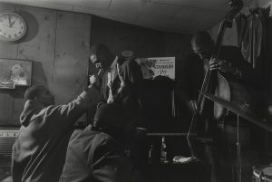 One man leans over to have a cigarette lit. A man on his right is playing an upright bass,
