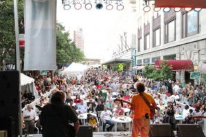 Image from the Rochester International Jazz Festival. People gather around tables on Gibbs Street and watch a band preform.