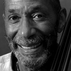 Close-up, black and white image of Ron Carter with his bass.