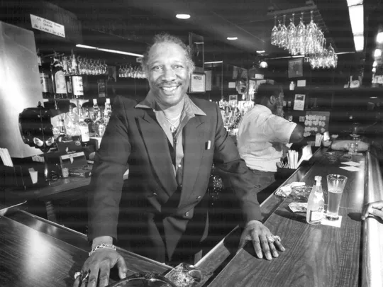 Ruth Shephard, smiling, stands behind the corner of his bar at Shep's paradise.