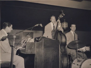 A black and white photo depicts a pianist, a bassist, and a drummer preparing to play.