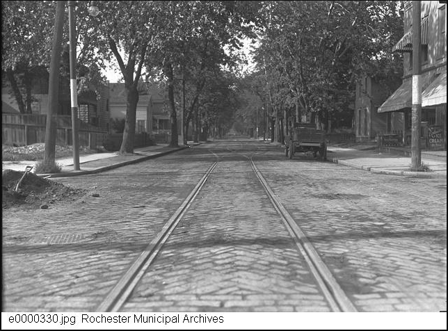 Clarissa Street in the late 1800s, originally named Caledonia. One-point perspective of the street paved with cobblestones. Trolly tracks are visible, and a cart is on the right hand side of the road. Leafy trees shade the street and well kept homes line the road.