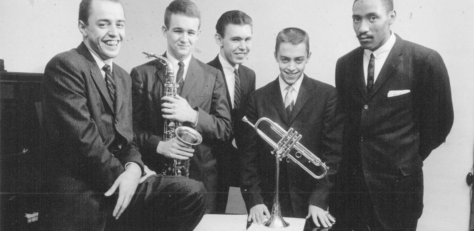 A group of musicians with their instruments smile for a portrait. They are all in suits and appear to be in their young 20s.