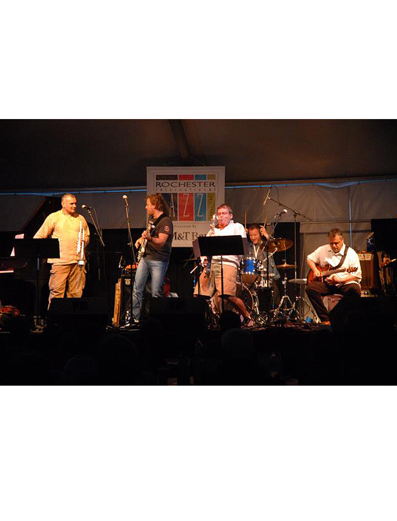 A jazz band of five preforms on stage at the Rochester International Jazz Festival.
