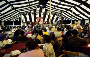 Locals gather around tables under a large tent, looking onwards towards the state, for the 1990 Pythodd Club Reunion